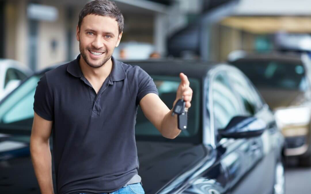 Man with car keys leaning on new car